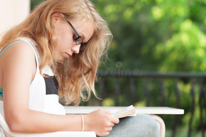 Blondynki Kaukaska nastoletnia dziewczyna czyta książkę obraz stock