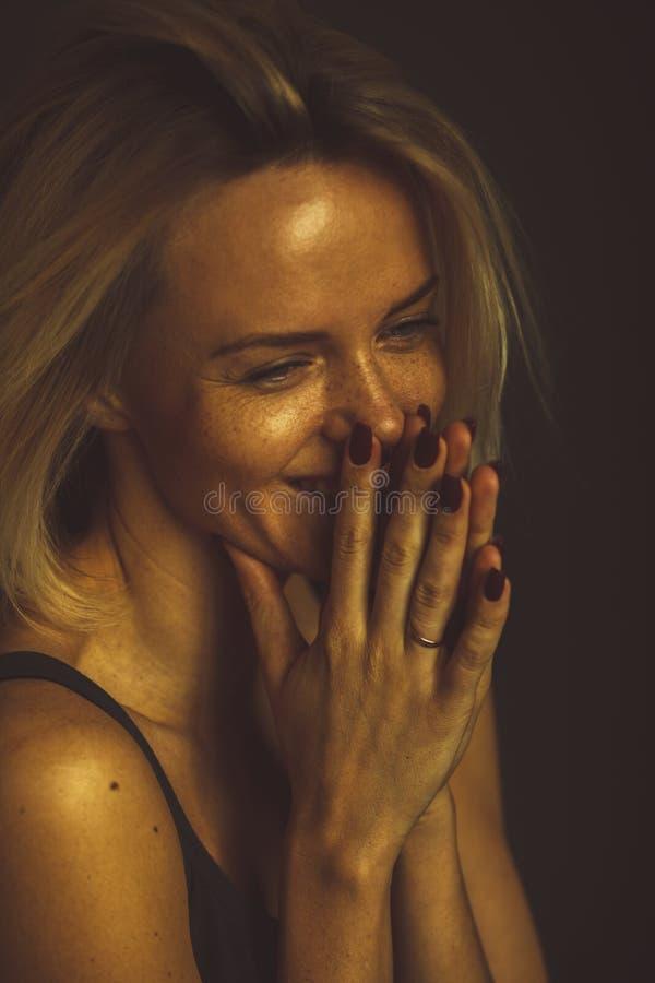 Blondynki kobieta śmia się, zamykający jej uśmiech z ona ręki obraz stock