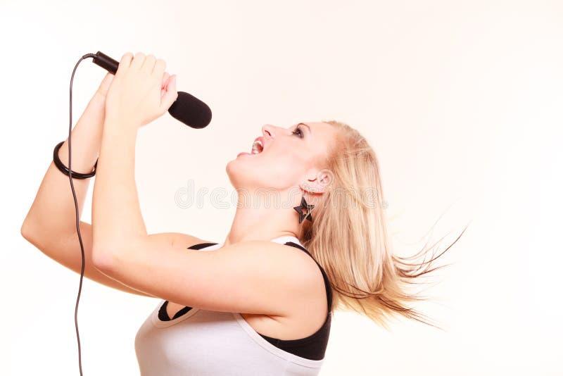 Blondynki kobieta śpiewa mikrofon, profilowy widok zdjęcie stock