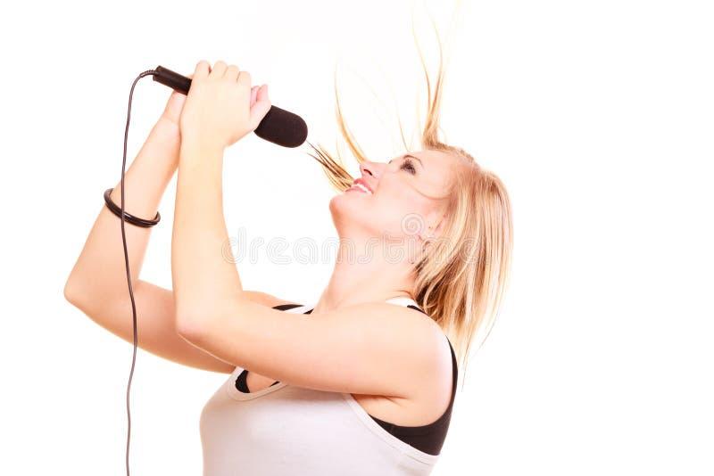 Blondynki kobieta śpiewa mikrofon, profilowy widok obrazy royalty free