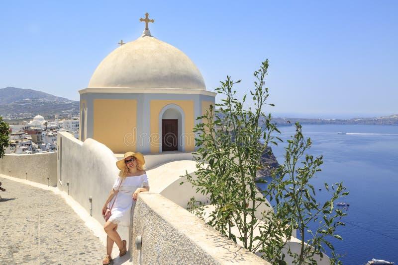 Blondynki kobieta blisko St Stylianos kościół w Fira, Santorini, Grecja zdjęcia stock