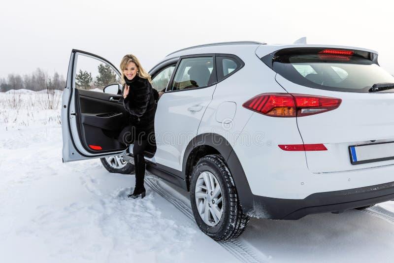 Blondynki kobieta dostaje z białego suv samochodu i patrzeje z powrotem fotografia stock