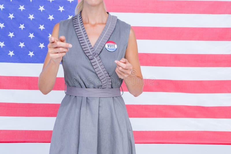Blondynki kobieta gestykuluje przed flaga amerykańską z odznaką obraz royalty free