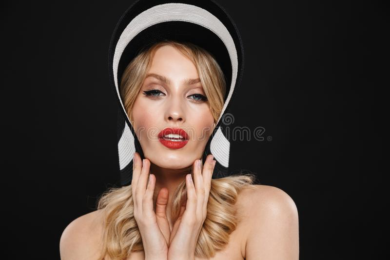 Blondynki kobieta jest ubranym kapelusz z jaskrawego makeup warg czerwony pozować odizolowywam nad czerni ściany tłem fotografia stock