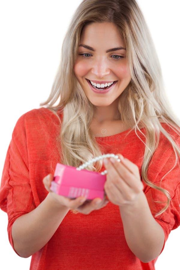 Blondynki kobieta odkrywa kolię w prezenta pudełku fotografia stock