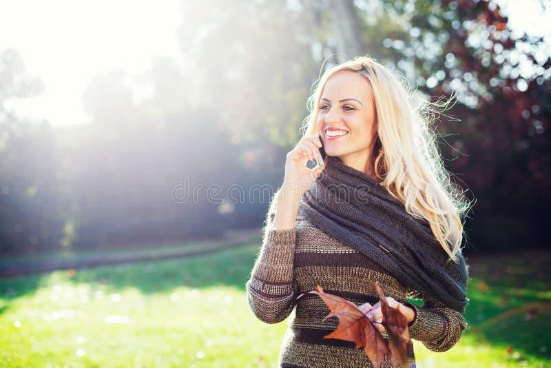 Blondynki kobieta opowiada na telefonie komórkowym zdjęcie stock