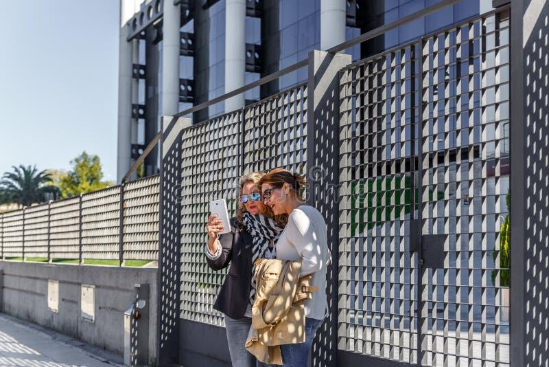 Blondynki kobieta pokazuje coś na pastylce inny partner zdjęcie royalty free