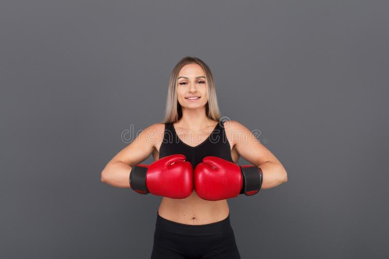 Blondynki kobieta pozuje będący ubranym bokserskie rękawiczki fotografia stock