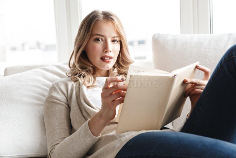 Blondynki kobieta pozuje siedz?cy indoors w domu czytelnicz? ksi??k? fotografia stock