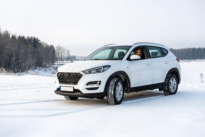 Blondynki kobieta siedzi w białym suv samochodzie w śnieżnym polu fotografia royalty free