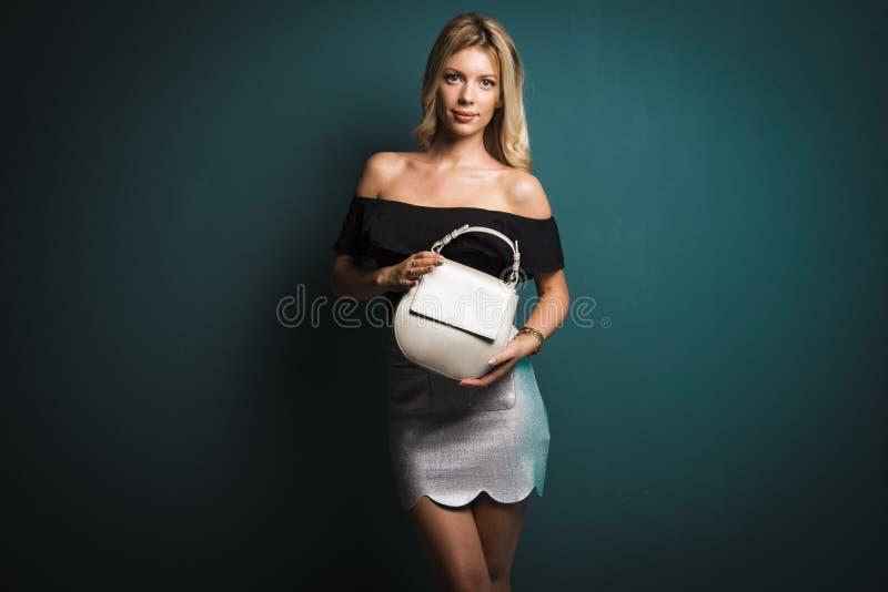 Blondynki kobieta trzyma małej kiesy na zmroku - szary tło fotografia stock