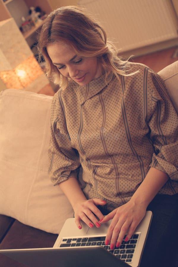 Blondynki kobieta używa jej laptop w domu obraz stock