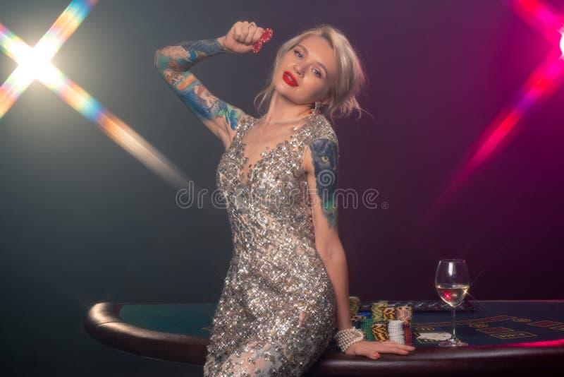 Blondynki kobieta uprawia hazard układy scalonych w jej rękach z piękną fryzurą doskonalić makijażem i pozuje z czerwienią kasyno zdjęcia stock