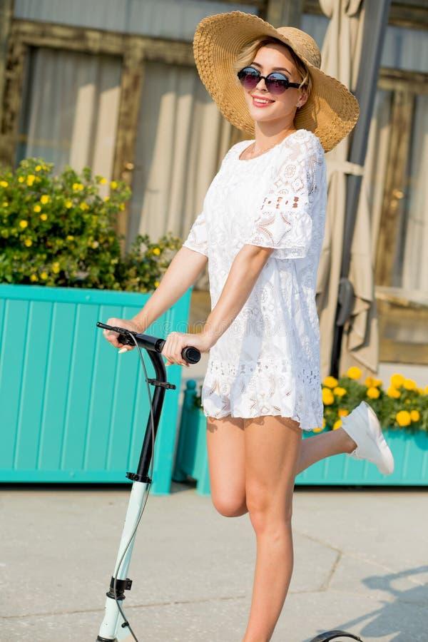 Blondynki kobieta w bielu kapeluszu na błękitnej kopnięcie hulajnoga jazdie na drodze i sukni obrazy stock