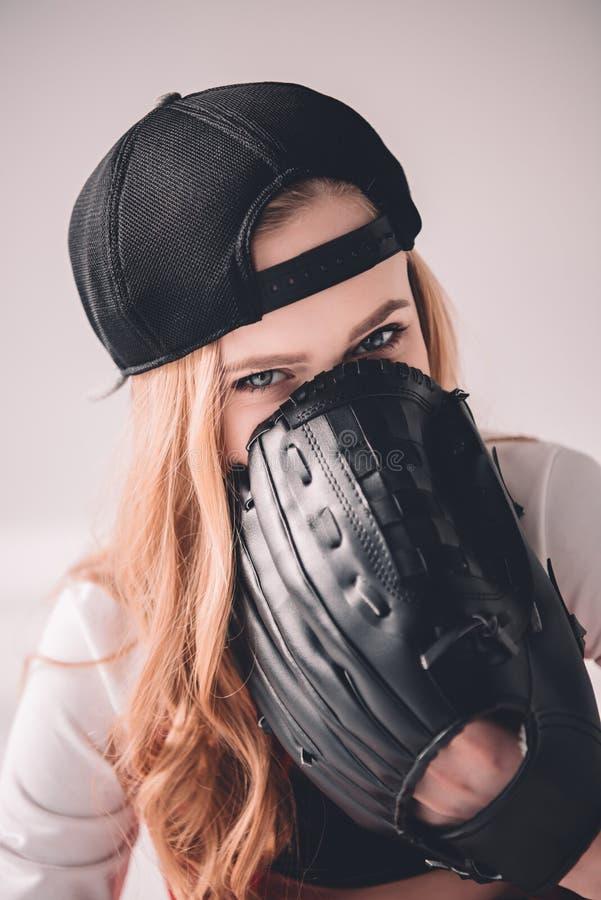 Blondynki kobieta w nakrętce chuje twarz z baseball rękawiczką fotografia stock