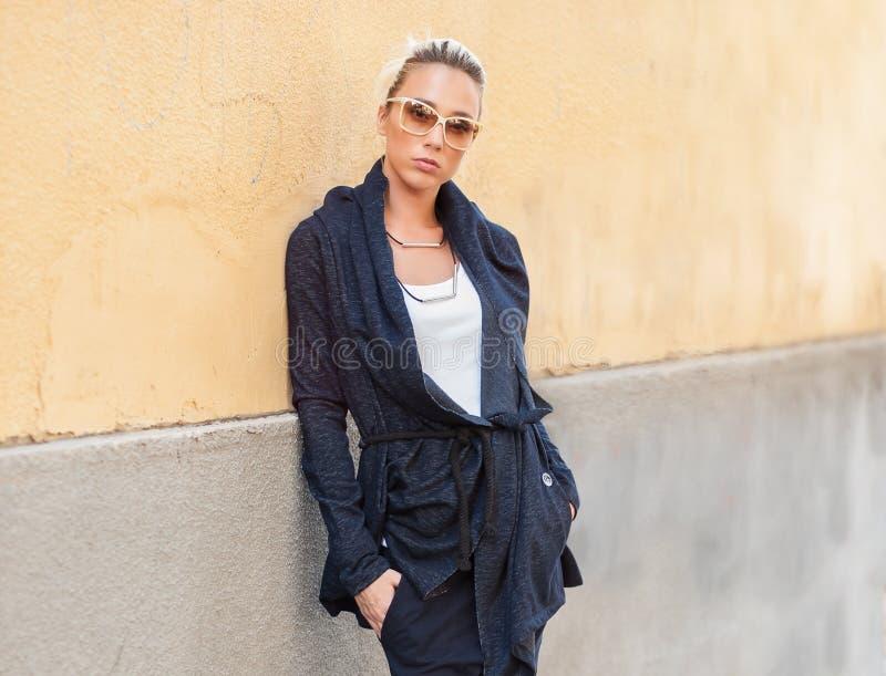 Blondynki kobieta z okularami przeciwsłonecznymi pozuje na ulicie obraz royalty free