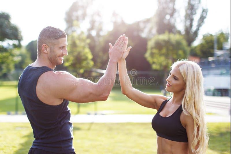 Blondynki kobieta z osobistym trenerem daje wysokości pięć obrazy royalty free