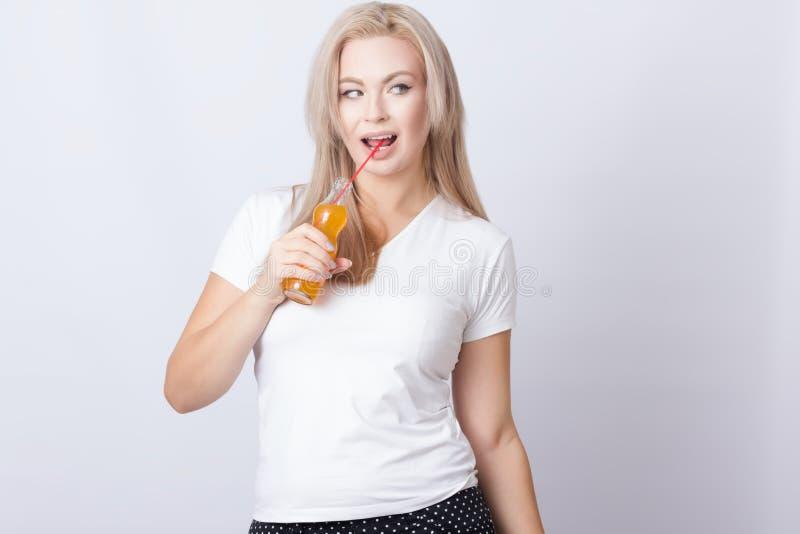 Blondynki kobieta z pomarańczową sodą w ona ręki fotografia royalty free