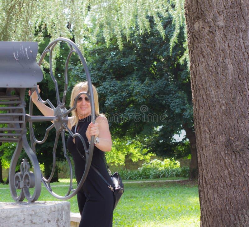 Blondynki kobieta z szkłami ubierał w czerni w drewnie odpoczywać na dobrze obrazy royalty free