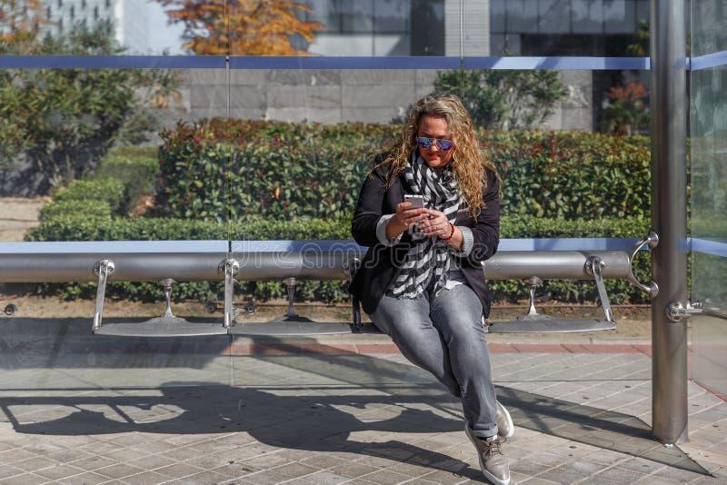 Blondynki kobiety dojrzały obsiadanie przy przystankiem autobusowym, patrzeje ostrożnie przy coś na jej telefonie komórkowym obraz stock