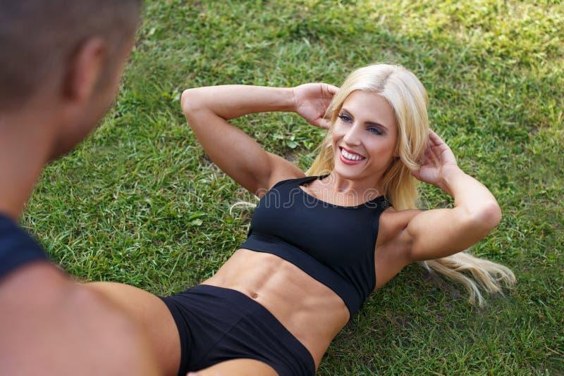 Blondynki kobiety dysponowany robić siedzi z osobistym trenerem z zdjęcie stock