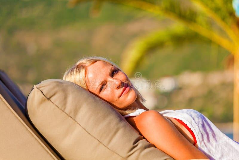 Blondynki kobiety lying on the beach na deckchair, cieszy się wakacje letnich obraz stock