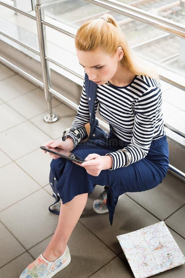 Blondynki kobiety obsiadanie przy stacją i patrzeć talerz przeciw tłu ściana szkło fotografia stock