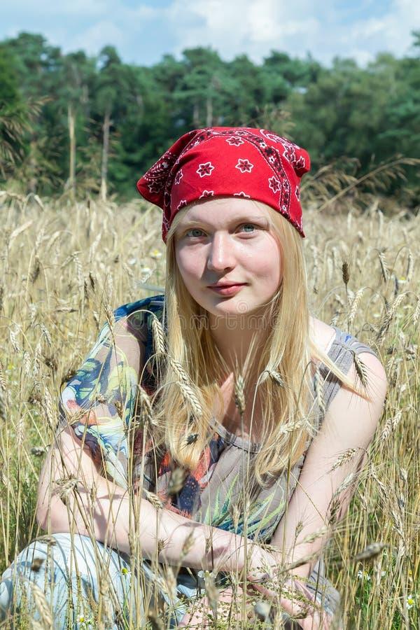 Blondynki nastoletniej dziewczyny obsiadanie w polu uprawnym zdjęcie stock