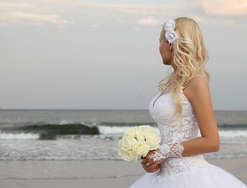 Blondynki panny młodej odprowadzenie na plaży. piękna kobieta patrzeje na oceanie w ślubnej sukni. obraz stock