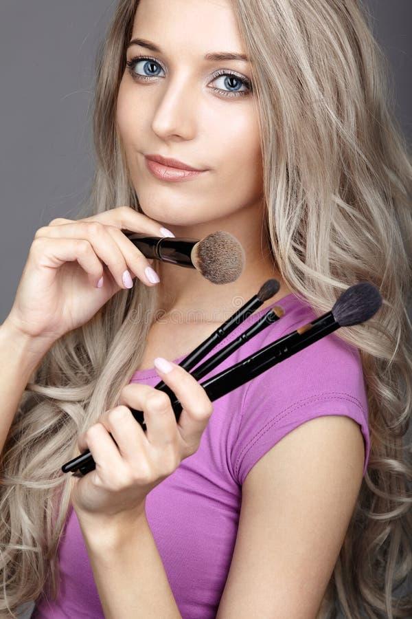 Blondynki piękna żeński stylista - visagist z makeup szczotkuje zdjęcie stock