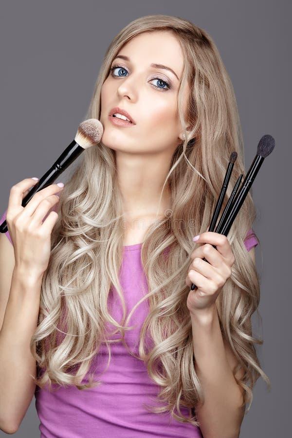 Blondynki piękna żeński stylista - visagist z makeup szczotkuje obrazy royalty free