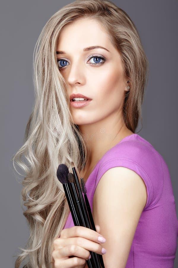 Blondynki piękna żeński stylista - visagist z makeup szczotkuje obrazy stock