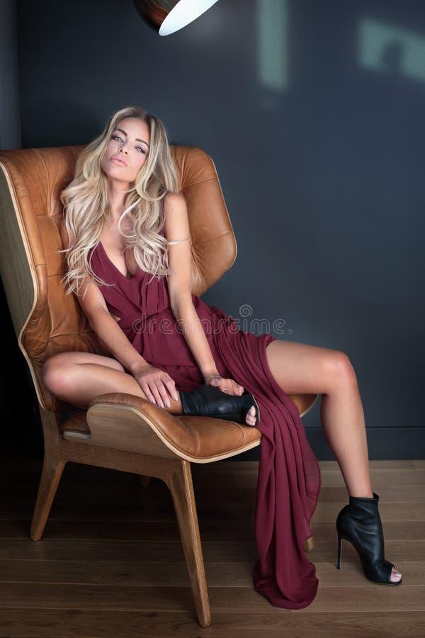 Blondynki piękna kobieta jest ubranym modną suknię obraz royalty free