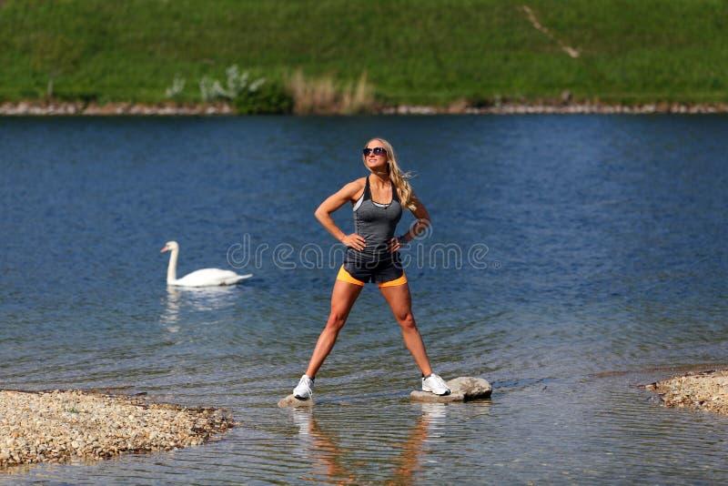Blondynki sprawności fizycznej dziewczyny pozycja przy rzeką fotografia stock
