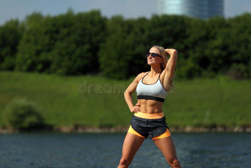 Blondynki sprawności fizycznej dziewczyny pozycja przy rzeką obrazy stock