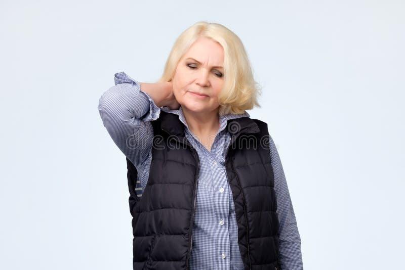 Blondynki starsza kobieta męczył z bólem w szyi zdjęcie royalty free