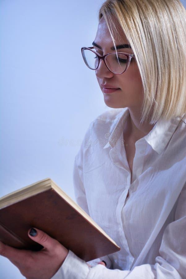 Blondynki studenckiej dziewczyny czytelnicza książka z szkłami na oczach fotografia royalty free