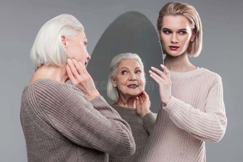 Blondynki z włosami dziewczyna męczy nieść ciężkiego lustro obrazy stock