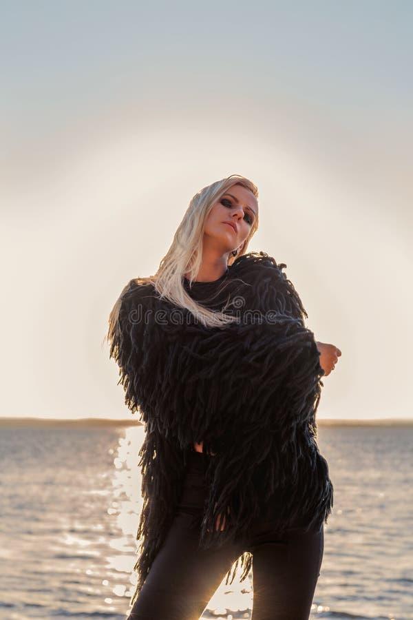 Blondynu model w czarnej kosmatej kurtce jest w mody pozie z wodą i położenia słońcem na tle fotografia stock