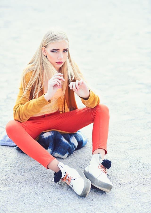 Blondyny modelują z gęstymi brwiami i rumieniącymi się policzkami siedzi na piaskowatej drodze Dziewczyna w jaskrawym stroju pozu obrazy stock