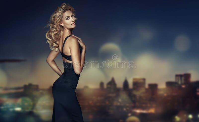 Blondyny modelują z długie włosy pozować w czerni sukni obraz stock
