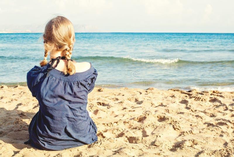 Blone-Mädchen auf tropischen Strandferien, weibliche Rückseite gegen Meer, Sand und Himmel lizenzfreie stockfotografie