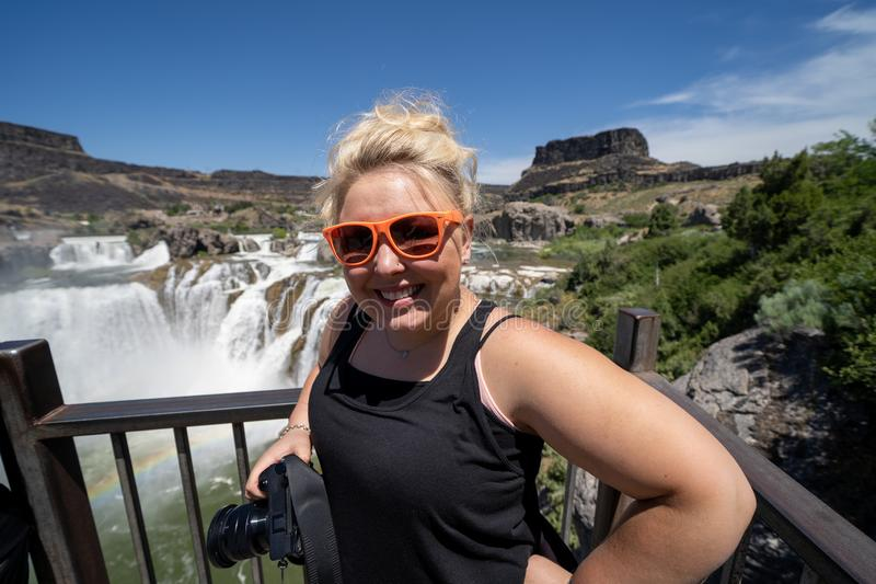Blone young adult woman poses with her camera at the overlook of Shoshone Falls in Twin Falls Idaho royalty free stock image