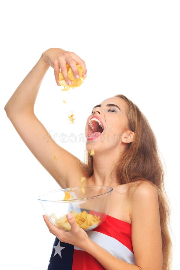 Blont äta för ung kvinna chiper för en potatis som isoleras på en vit bakgrund royaltyfria foton