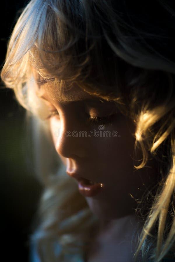 Blont behandla som ett barn flickan i soluppgångljuset royaltyfri fotografi