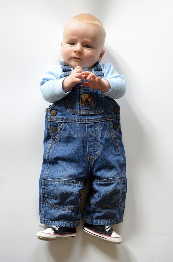 Blont behandla som ett barn pojken i jeans royaltyfri foto