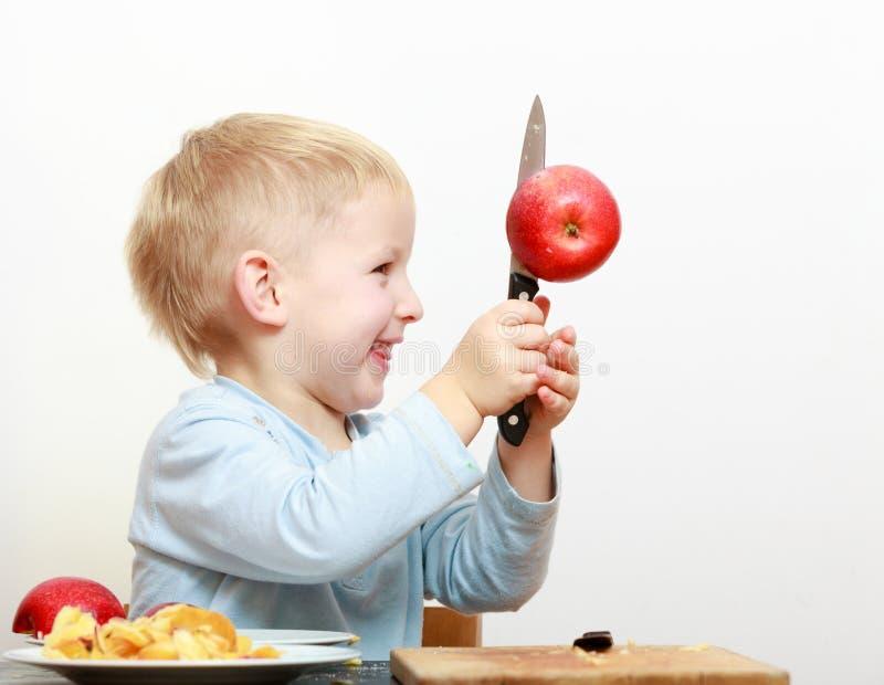 Blont förskolebarn för pojkebarnunge med äpplet för frukt för klipp för kökkniv royaltyfria bilder