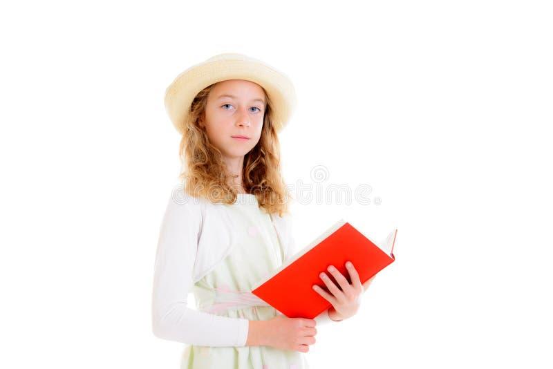 Blont flickahår i den vita klänning- och sugrörhatten som läser den röda boken arkivfoton