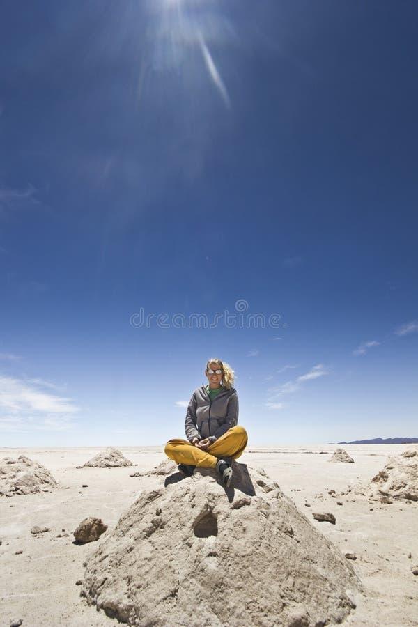 Blont flickasammanträde på salt hög på Salar Uyuni, Bolivia royaltyfri bild