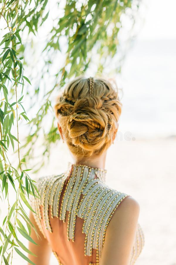Blont blont hår göras professionellt med flätade trådar i en storartad frisyr för en sommarbröllopbild av en brud eller royaltyfri fotografi